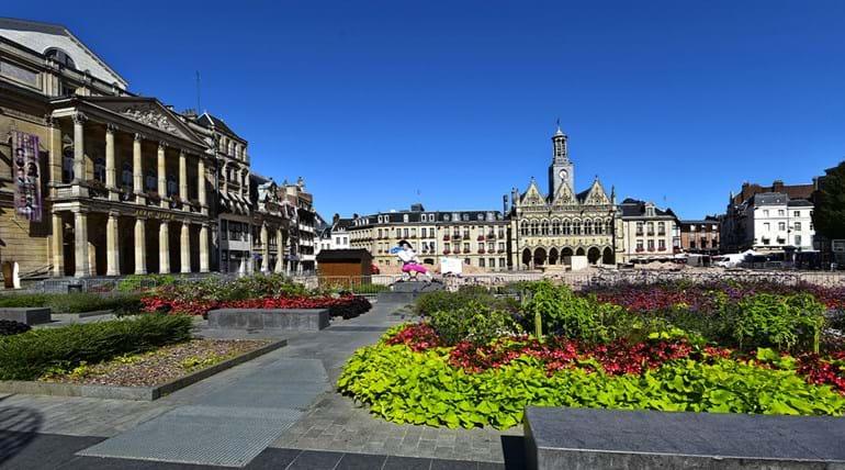 Town square surrounded by French architecture and garden in the foreground